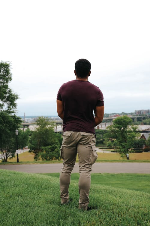 Sporty black man looking at village while standing on grass