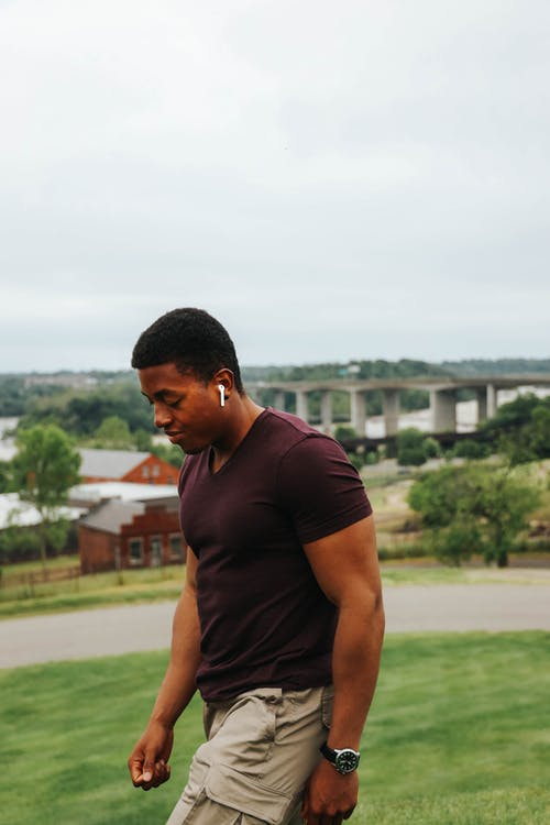 Handsome young black muscular male in casual clothing looking at camera with toothy smile while standing on lawn in park