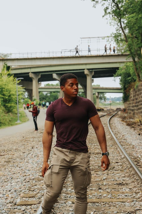 Man in Maroon Crew Neck T-shirt and Brown Shorts Standing on Train Rail