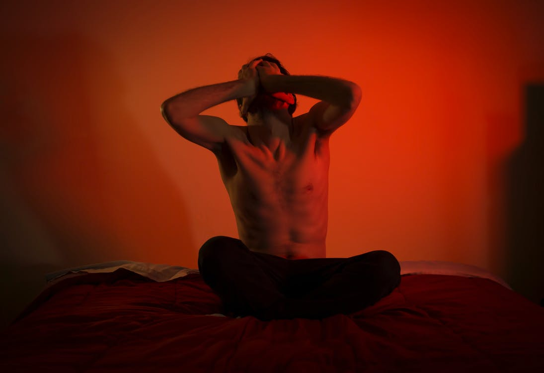 Topless Man in Black Pants Lying on Bed