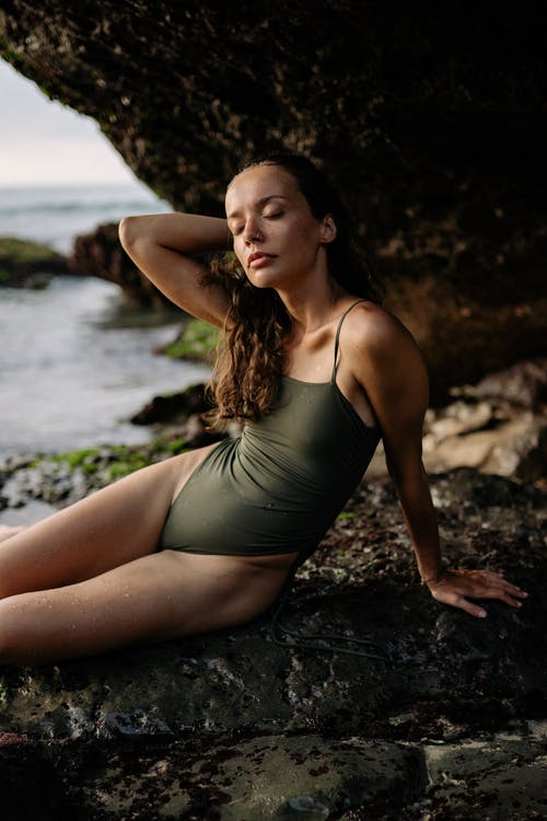 Young slim lady in swimwear sitting and leaning on stone in front of rock and touching hair while resting on seashore