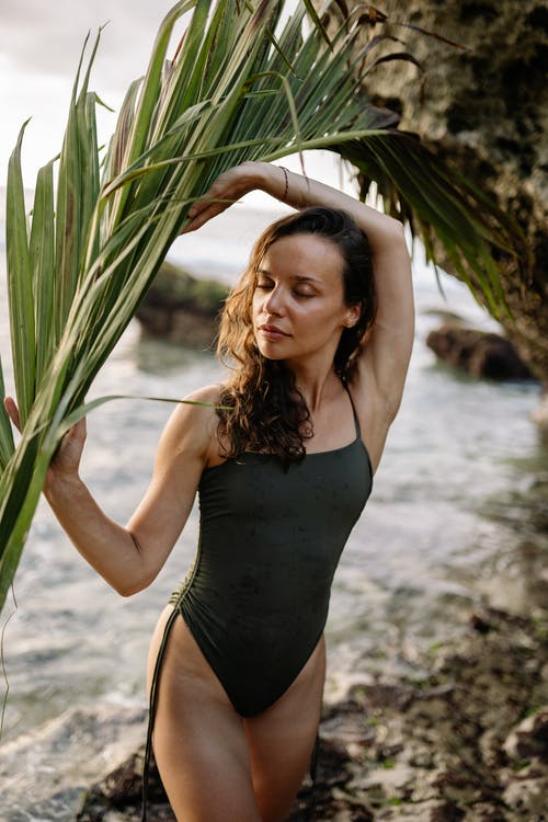 Young suntanned lady in swimsuit with palm branch on beach