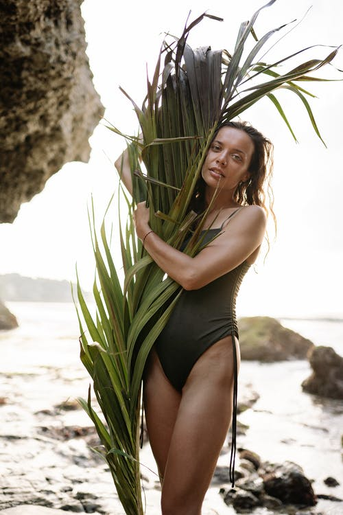 Young slender female in swimming suit with big palm branch
