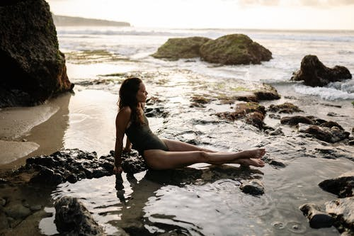 Slim woman in swimsuit sitting on rocky ocean shore