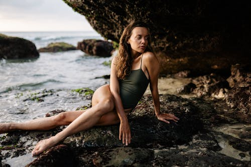 Young model in bathing suit sitting on stone near sea