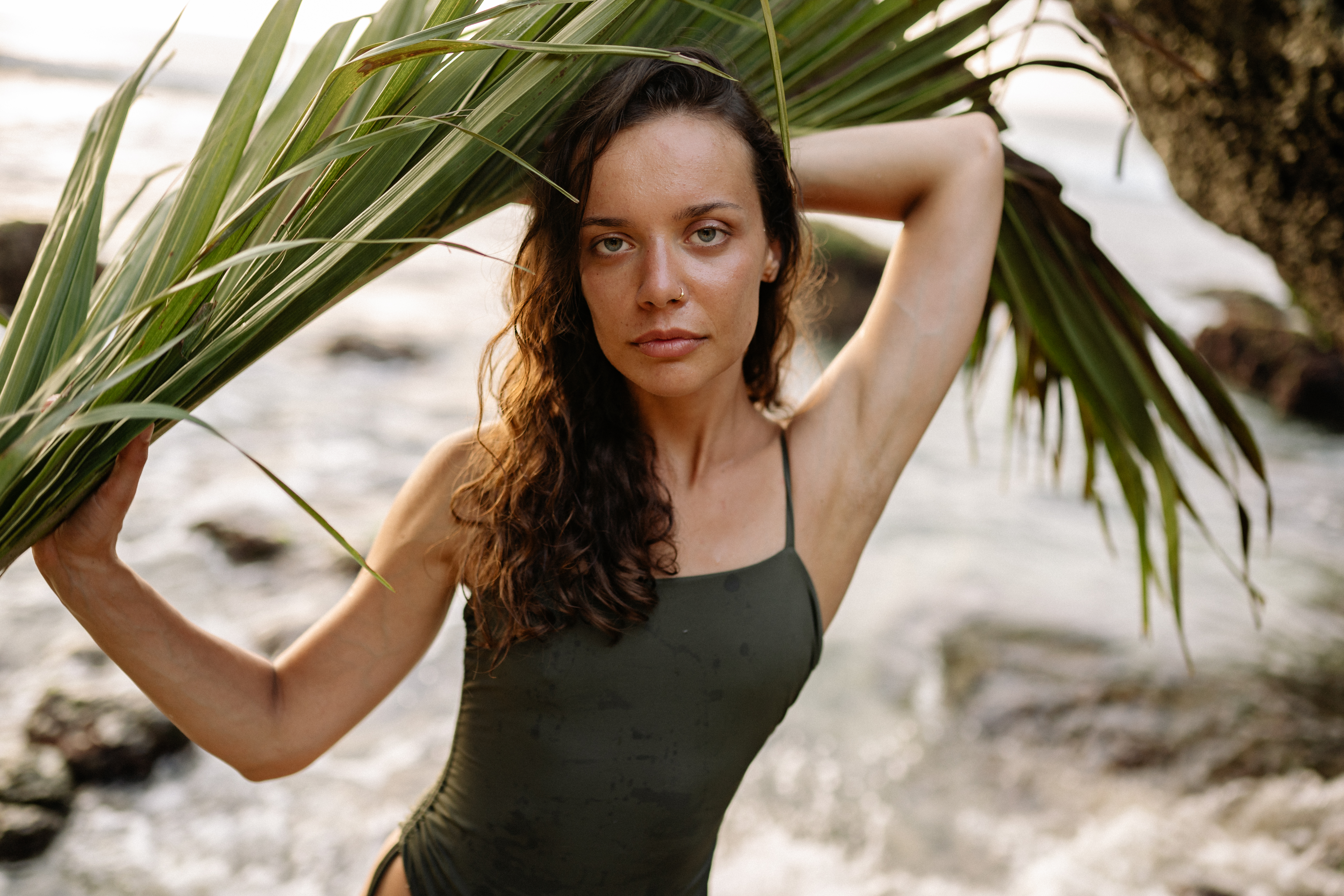 confident woman in swimsuit with palm leaf looking at camera