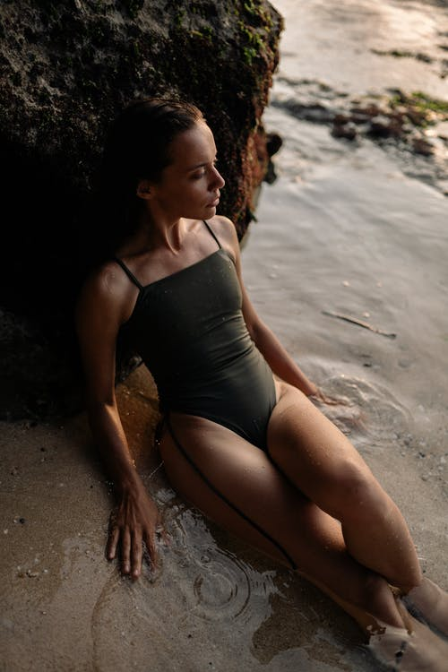 From above of young slender female model in modern swimsuit leaning on rock and looking away while enjoying vacation on wet sandy beach at sundown
