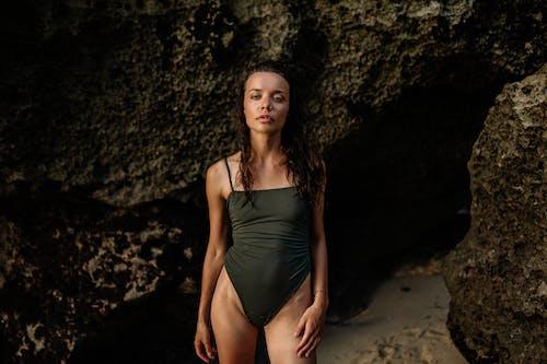 Fit suntanned woman in swimsuit standing near seashore rocks