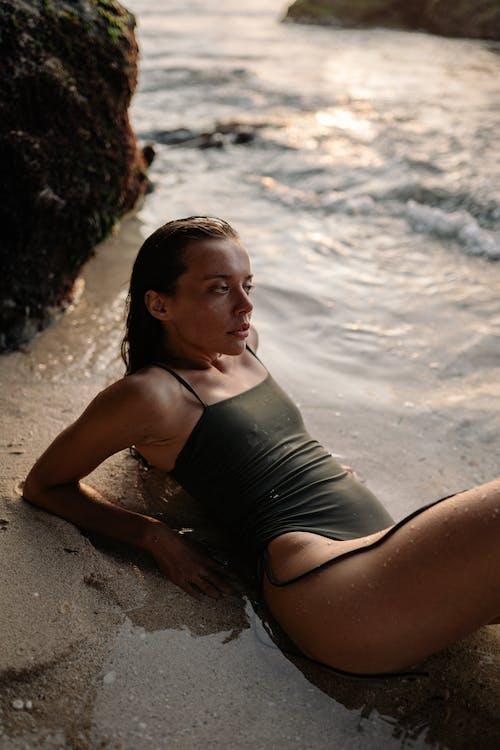 Young slender woman in bathing suit relaxing on ocean shore