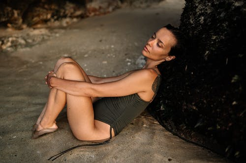 Side view of young slim female in trendy swimsuit leaning against rough rock while enjoying warm tide at sandy beach of sea resort at sundown