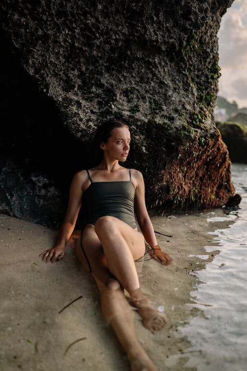 Full body emotionless female in swimwear relaxing alone on wet sand in sea water while leaning on rocky cliff in sunny evening