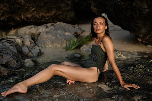 Slim young woman in swimsuit sitting on stony surface