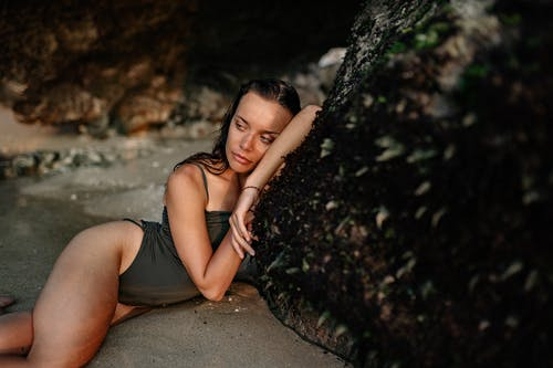 Relaxed woman in swimsuit leaning on rock on beach