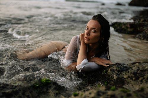 Sensual woman in shirt and bikini lying on sandy beach in water