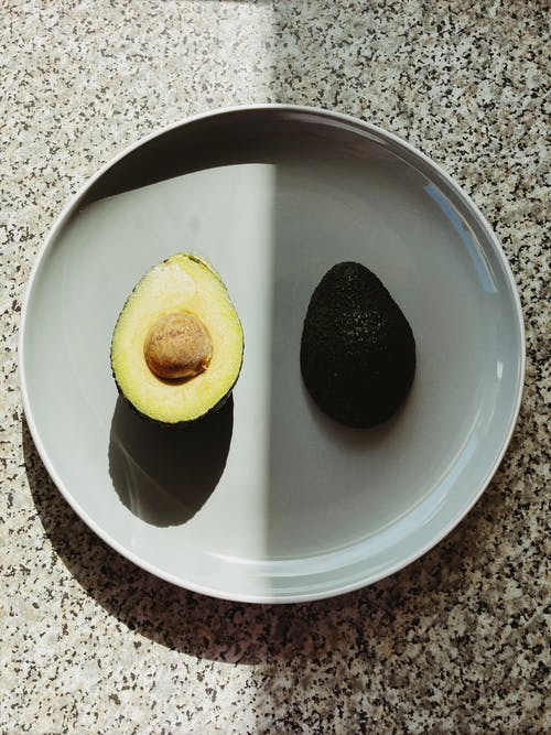 Top view of halves of fresh avocado placed on gray plate with half in shadow