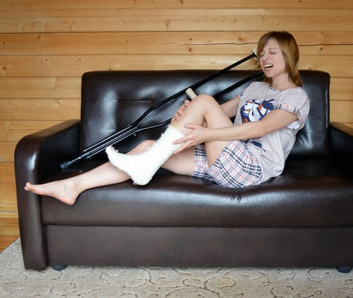 Side view full body of young female feeling pain in leg in cast while sitting with crutch