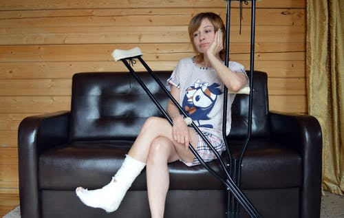 Unhappy woman with trauma in leg sitting on sofa and leaning on crutches
