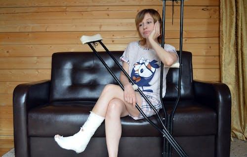 Young sad woman with broken leg on sofa