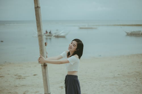 Woman in White Shirt and Blue Skirt Holding Brown Wooden Stick