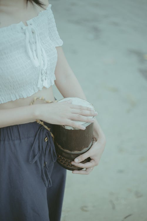 Woman in White Knit Shirt and Blue Skirt Holding Brown Ceramic Mug