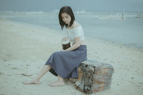 Woman in White Shirt and Blue Skirt Sitting on Brown Rock
