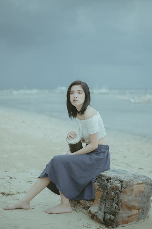 Woman in White Shirt and Blue Skirt Sitting on Rock by the Sea