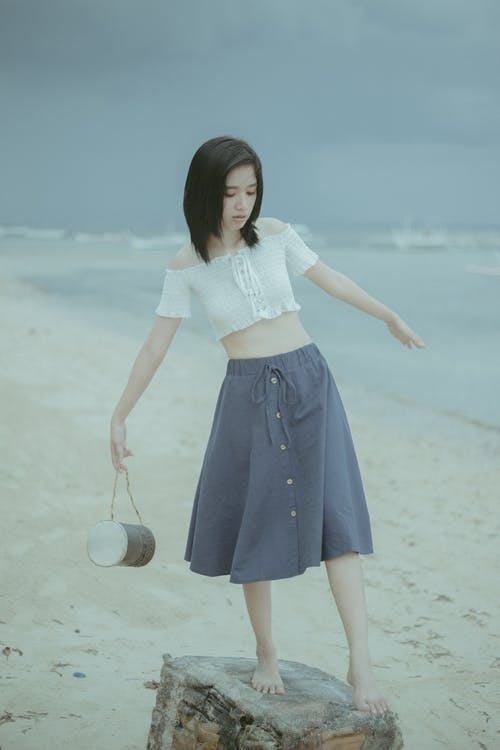 Woman in White Shirt and Blue Skirt Holding a Ball