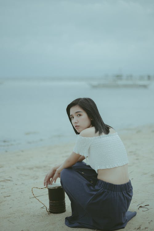 Woman in White Knit Sweater and Black Skirt Sitting on Gray Sand