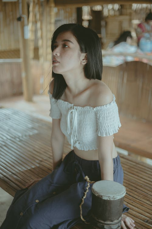 Woman in White Off Shoulder Shirt and Black Pants Sitting on Brown Wooden Floor