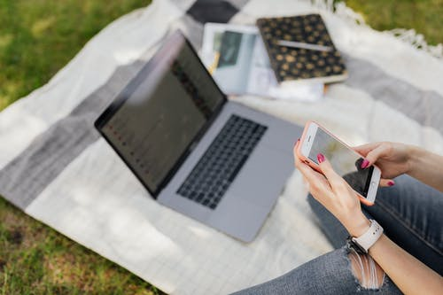 Crop female student chatting online on mobile in park