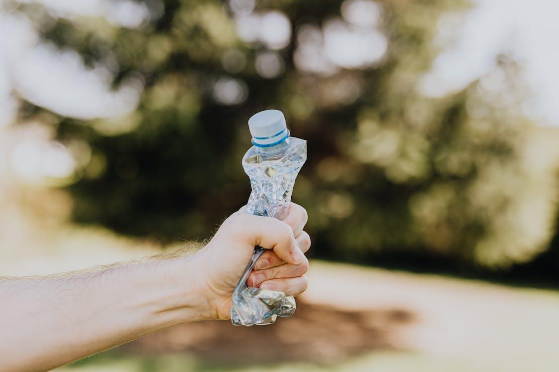 Crop man crushing plastic bottle