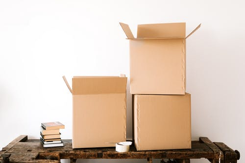 Opened cardboard boxes and stack of books placed on wooden shabby table near tape with scissors against white plain wall
