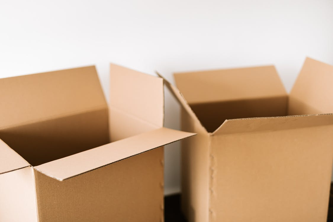 Opened carton boxes placed on dark surface against white plain wall in daylight before moving out