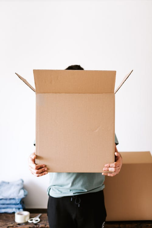 Unrecognizable man with carton box in apartment