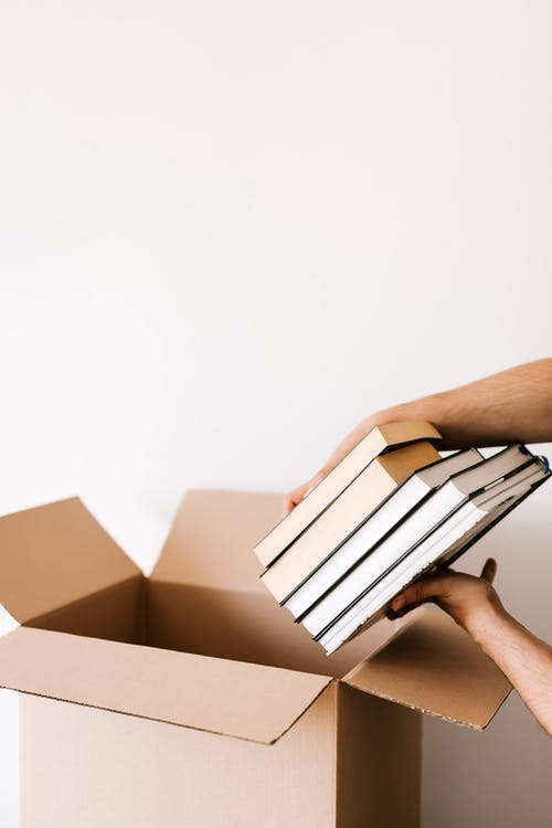 Crop person packing stack of books in carton box