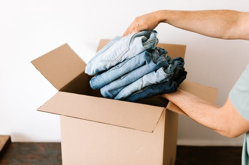 Crop man packing casual clothes into carton box