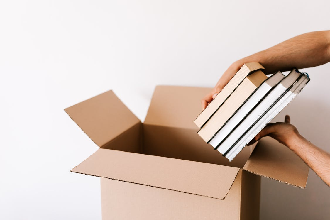Crop unrecognizable male packing staked books into carton box while standing against white wall during relocation