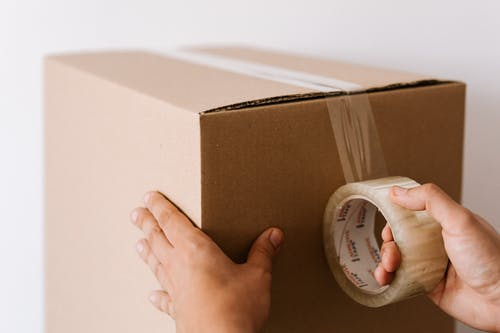 Crop faceless male sealing packed carton box with tape against white wall in daylight during relocation