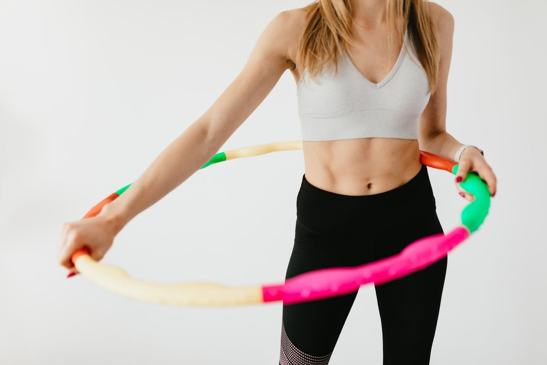 Crop faceless fit lady in black leggings and sports bra practicing fitness exercises with hula hoop against gray background