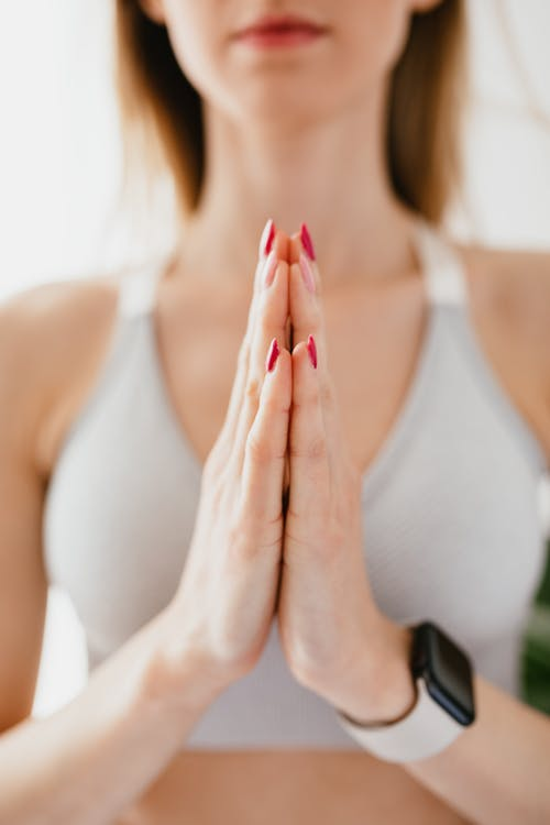 Crop calm sportswoman meditating and showing namaste gesture