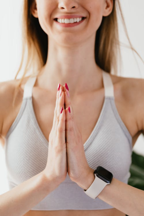 Crop smiling fit female wearing gray sports bra and modern smartwatch standing with hands folded in namaste gesture while practicing yoga on gray background