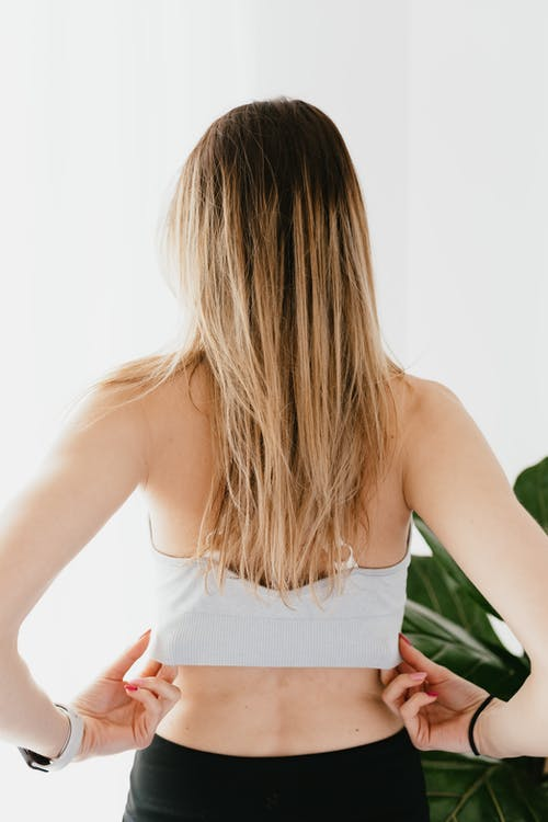Back view anonymous fit lady standing against gray wall and touching sports bra while resting after training