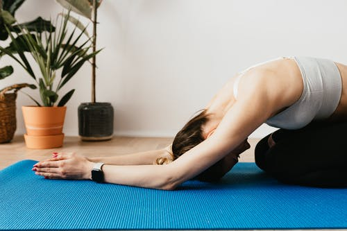 Flexible sportswoman practicing yoga on mat