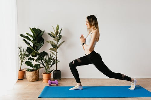 Side view of fit lady in sports clothes and wristwatch standing in Anjaneyasana pose while practicing yoga on mat near dumbbells and potted plants at home and looking away