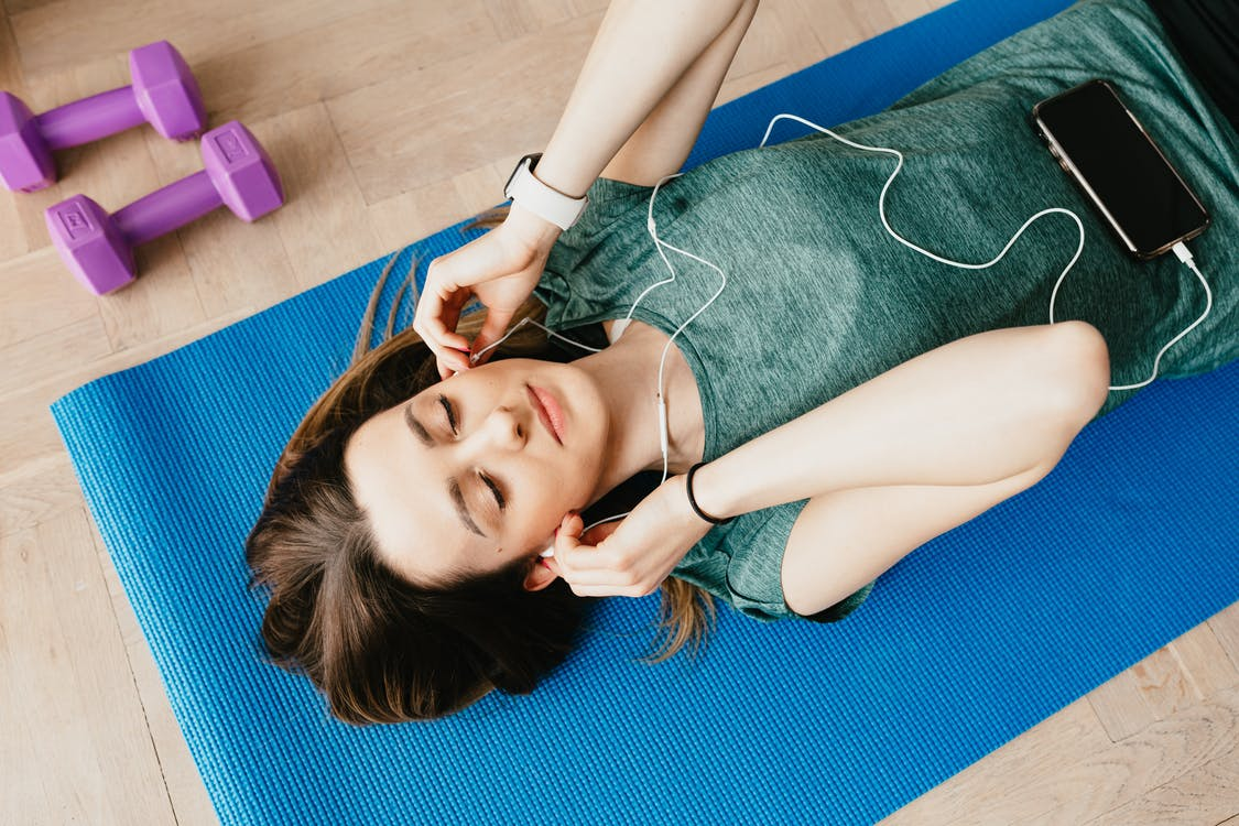 Sportive lady in earphones listening to music chilling on mat
