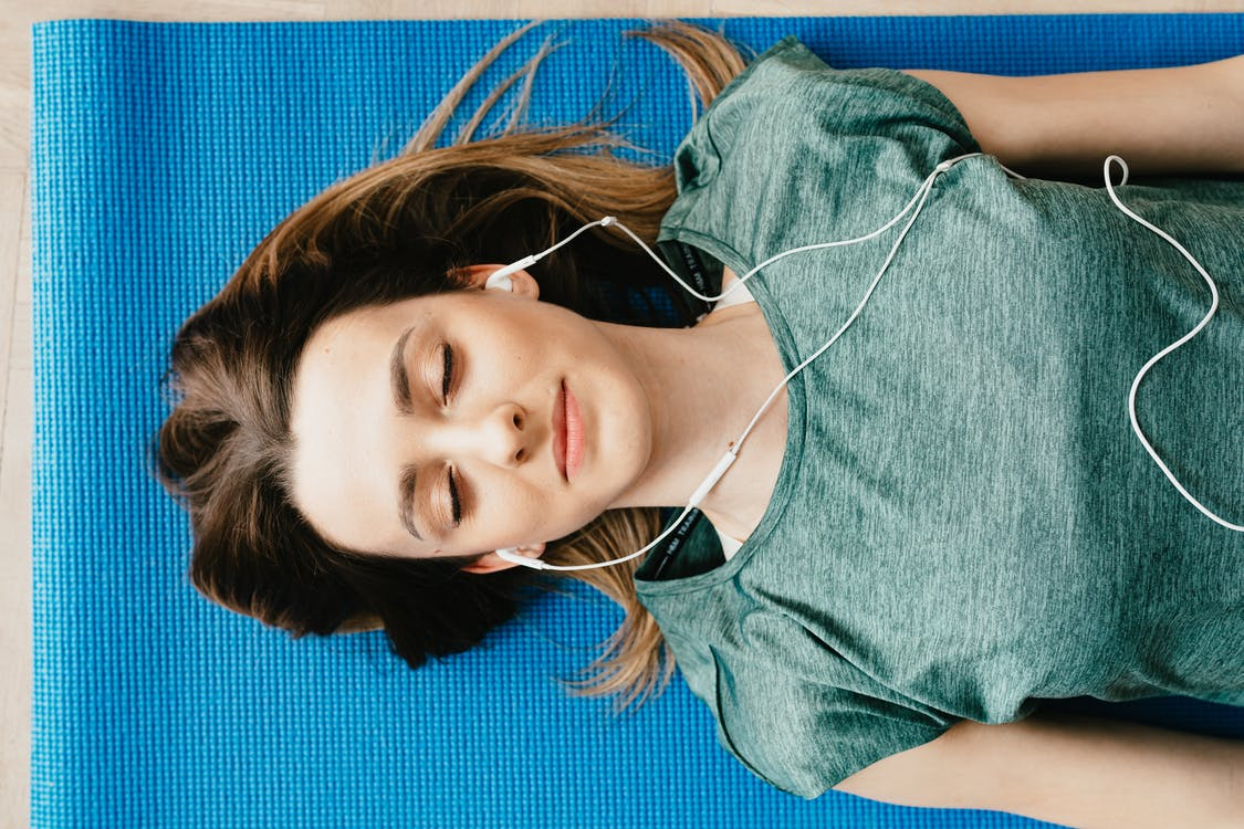 Tranquil woman resting on yoga mat in earphones at home