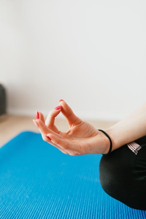Crop unrecognizable woman meditating in Lotus pose at home