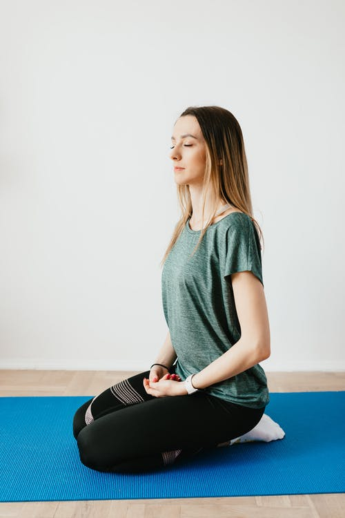Side view of young slim female in sportswear sitting in Virasana pose with closed eyes while practicing yoga at home