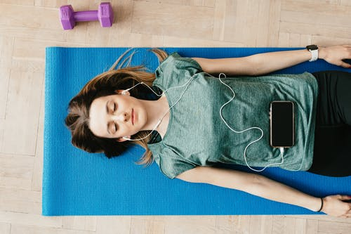 Peaceful woman in earphones resting in Shavasana pose at home