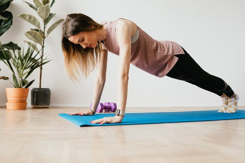 Fit woman in smart watch standing in Plank pose indoors
